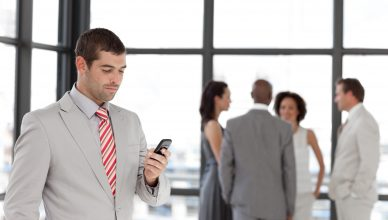 Smiling businessman holding a phone at workplace with his colleagues